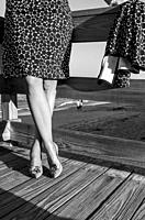 A black and white image taken from the waist down of a woman dressed in 1950's vintage octagon patterned dress, nylon stockings, and stiletto heels st...