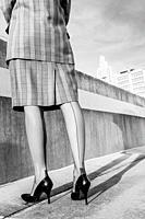 Back view of woman wearing a plaid business suit , Cuban heeled nylon seamed stockings, and vintage crocodile patterned stiletto pumps standing on the...