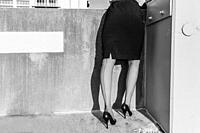 Back view of woman wearing a dark A-line skirt, Cuban heeled nylon seamed stockings, and black stiletto pumps standing in a corner against a concrete ...