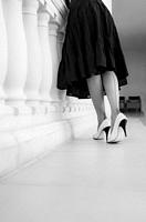 A black and white image of a woman seen from the back and waist down wearing a dark flowing dress, 1950's seamed Cuban heeled nylon stockings, and two...