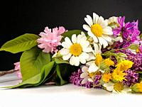 Daisies and flower bouquet on black background.