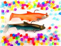 Two fish hooks in the shape of a fish and brightly colored plastic pieces on white background.