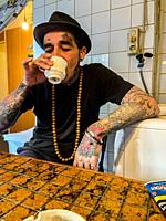 Tilburg, Netherlands. Man with an abundance of tattoo's drinking a cup of tea on his kitchen table.