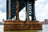 Detail of Pillar of Manhattan Bridge against cityscape of New York City. Steel Abutment With Bolt and Rivet Connections. Engineering and architecture.