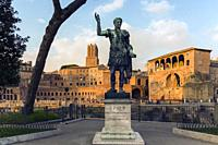 Rome, Italy. Statue of the Emperor Trajan with Trajan's Forum behind. The forum dates from the second century AD. The tower, centre, is the 13th centu...