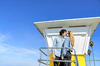 A young couple interlaced in front of a vintage lifeguard tower.
