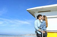 A young couple interlaced in front of a lifeguard tower.