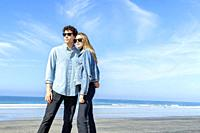 Young couple wearing sunglasses at the beach.