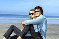 Young couple wearing sunglasses and sitting at the beach.