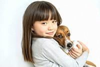 EIght year old girl embracing her dog pet.