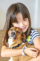 Portrait of eight year old girl hugging her pet dog.