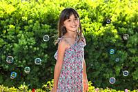 Eight year old girl surrounded by soap bubbles.
