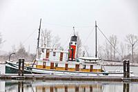 Steam powered tugboat at dock in a snow shower along the Steveston waterfront in British Columbia Canada.