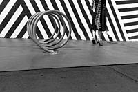 A black and white image of an anonymous woman wearing a black skirt, flowing patterned scarf, seamed Cuban heeled stockings, and sequined stiletto hee...