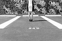 A black and white image of an anonymous woman wearing a black and white striped dress, seamed Cuban heeled stockings, and sequined stiletto heels stan...
