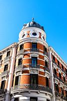 Old luxury residential brick building with balconies in historic centre of Madrid. View against blue sky. Concept rent regulation.