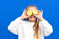 Overjoyed blond haired girl in white sweater smiling while covering eyes with bright lemon slices isolated on blue background. High quality photo.