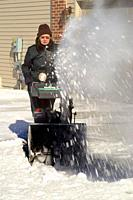 Adult clearing snow from sidewalk and walkway with a snowblower.