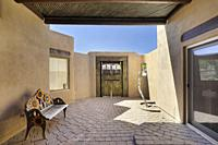 Courtyard with adobe walls and brick paving with wooden doors in a luxury Southwestern home.