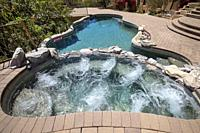 Hot tub with swimming pool and terraced patio at a luxury home in a desert environment.