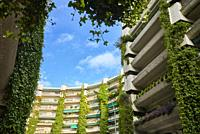 The Oasis building, by Fernando Higueras, is a residential building made of concrete with huge vines hanging from the balconies. Madrid, Spain.