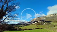 Loquiz Mountain range and Aramendia village with clouds in a countryside time lapse view. Navarre, Spain, Europe.