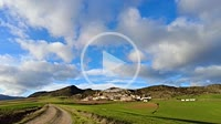Rural and agricultural green cereal landscape and village in a time lapse view. Piedramillera village, Navarre, Spain, Europe.