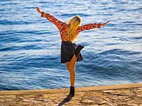 Joyful young woman near sea balancing on one leg flying short skirt