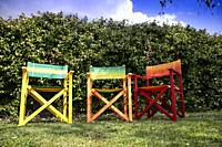 Set of small colored wooden chairs in a garden in the relaxation area.