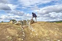 A visitor contemplates the Dolmen of San Adrián. Granucillo de Vidriales. Benavente and the Valles region. Zamora. Castile and Leon. Spain.