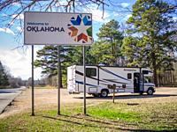 Road-sign welcomes those entering into Oklahoma with RV sitting in parking lot behind it, Oklahoma.