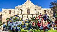 Wreaths of flowers place out in front of the iconic facade of the Alamo Mission, San Antonio, TX.