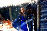 Beautiful girl in a blue stole stands next to a horse near wooden buildings on a snowy winter day.
