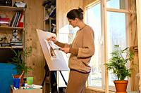 Girl artist draws on an easel at home, molubert stands at the window.