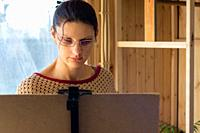 Portrait of an artist at work, a girl draws a drawing on an easel by the window, close-up.