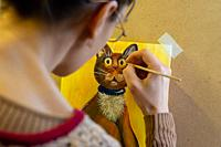 The artist paints a drawing of a cat on an easel with acrylic paints, a view from the artist's back.