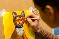 The artist draws with acrylic paints a drawing of a cat on an easel, close-up.