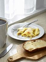 A kitchen counter with scrambled eggs, toast, coffee, and streaks of sunlight.