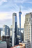 A skyline photograph of NYC featuring the Freedom Tower and blue skies.