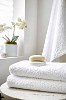 A stack of white towels in a spa setting with soap and an orchid.