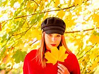 Young woman is holding big leaf in hand