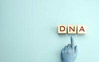 abbreviation DNA on wooden square blocks. A hand in a blue glove points to an object, blue background, copy space.