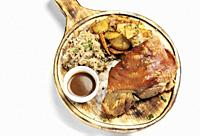 SCHWEINSHAXE traditional german pork knuckle with sauerkraut and potatoes meal on white background.