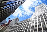 Low angle view of American flag and skyscrapers against sky in New York City. Finance, business and technology background.