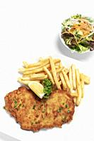 german breaded pork schnitzel with french fries on white studio background.