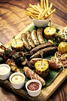 organic mixed grill barbecue meat platter rustic set meal with sausages, skewers, side dishes and sauces.