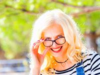 Attractive blonde mid-age woman looking over glasses flirting