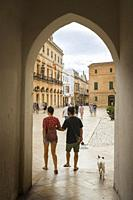 A young couple walking their dog through the old town of the Ciudadela, Menorca