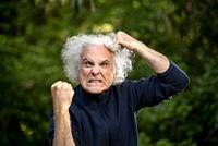A grey haired 68 year old man making a face and pulling his hair out. ,.