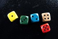 Representation of a set of colored game dice on a black background.